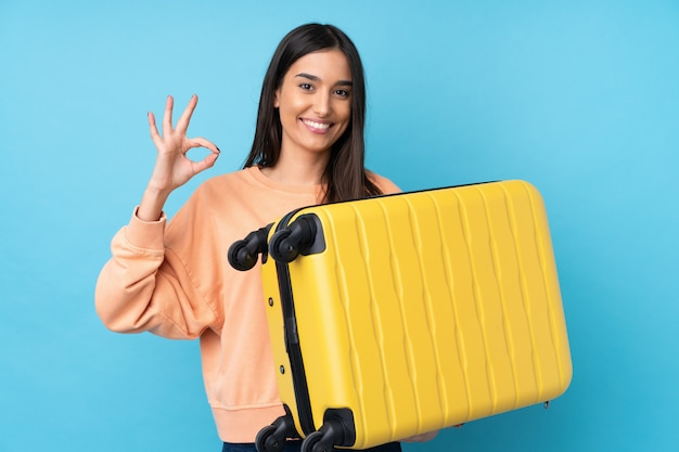 Young brunette woman over isolated blue wall in vacation with travel suitcase and making ok sign Premium Photo
