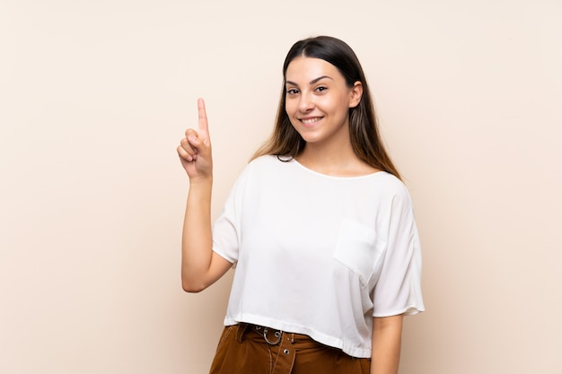 Young brunette woman showing and lifting a finger in sign of the best Premium Photo
