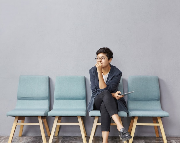 Young brunette woman sitting in waiting room Free Photo