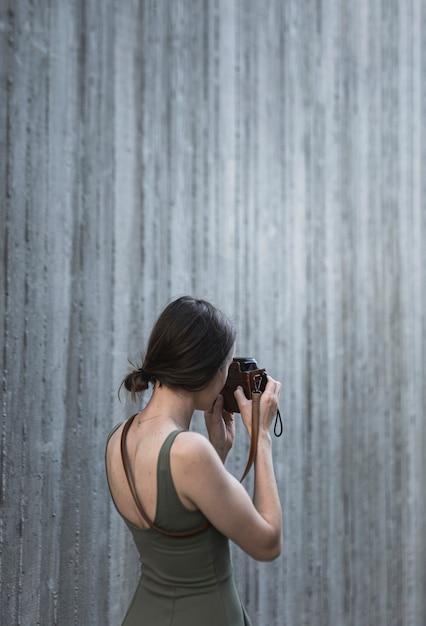 カメラで撮影する若いブルネットの女性 無料写真
