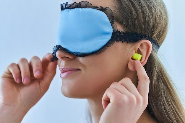 Молодая брюнетка использует затычки для ушей и маску для лучшего сна и сладких снов Premium Фотографии