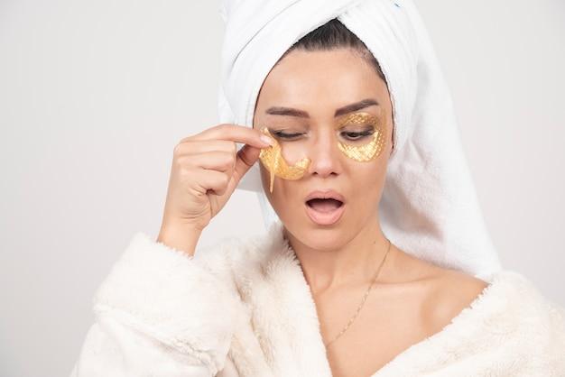 화장품 눈 패치를 적용하는 목욕 가운을 입고 젊은 갈색 머리 여자 무료 사진