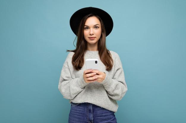 검은 모자와 카메라를보고 스마트 폰 들고 회색 스웨터를 입고 젊은 갈색 머리 여자 프리미엄 사진