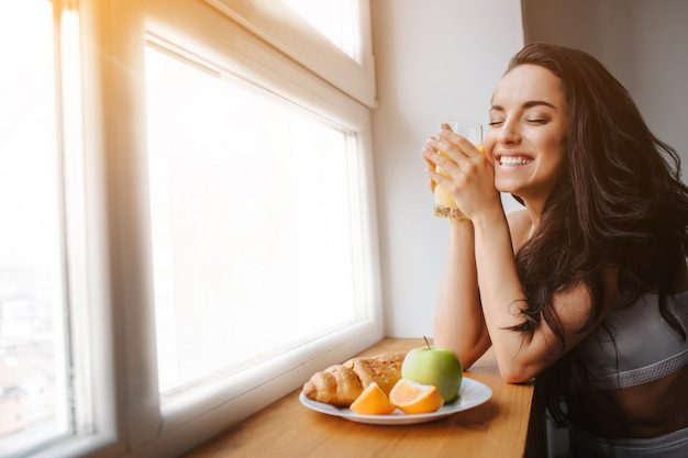 Young brunette woman in white underwear has breakfast by a wooden windowsill. a young female model e