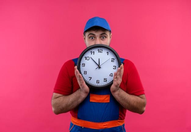Giovane costruttore in uniforme da costruzione e berretto che tiene l'orologio da parete che nasconde il suo volto dietro di esso sbirciando sorpreso Foto Gratuite
