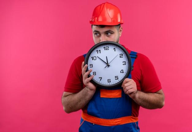 Giovane costruttore in uniforme da costruzione e casco di sicurezza che tiene orologio da parete che si nasconde dietro di esso che dà una occhiata sopra Foto Gratuite