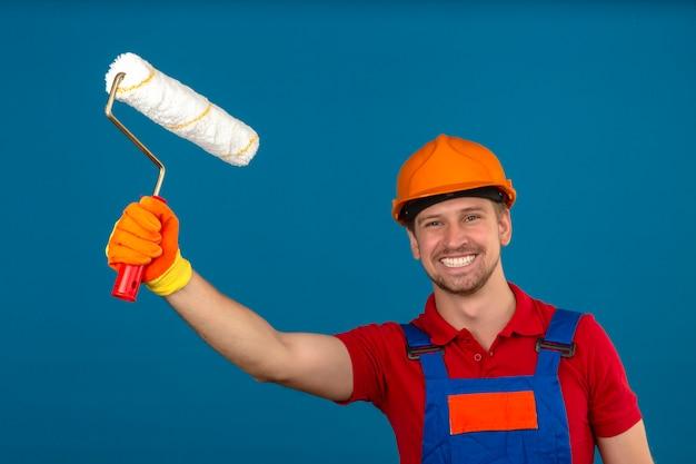 Молодой строитель человек в строительной форме и защитный шлем, держа валик и с большой улыбкой на лице над синей стеной Бесплатные Фотографии