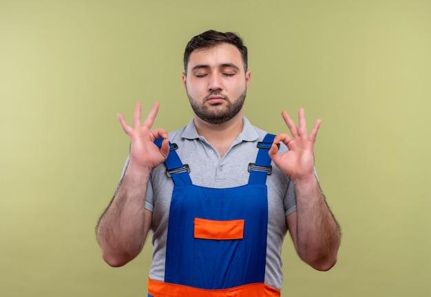 目を閉じてリラックスし、指で瞑想のジェスチャーをする建設制服の若いビルダー男 無料写真
