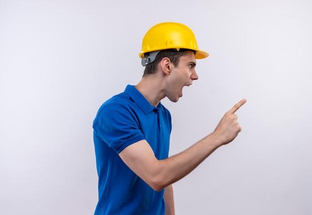 Il giovane costruttore che indossa l'uniforme da costruzione e il casco di sicurezza indica con rabbia a sinistra con l'indice Foto Gratuite