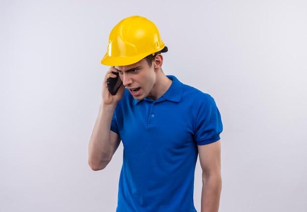 L'uomo del giovane costruttore che indossa l'uniforme della costruzione e il casco di sicurezza parla con rabbia al telefono Foto Gratuite