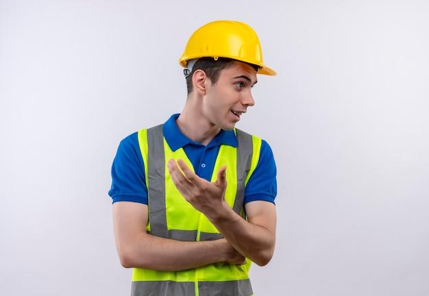 Chiede che indossa l'uniforme da costruzione e il casco di sicurezza del giovane costruttore Foto Gratuite