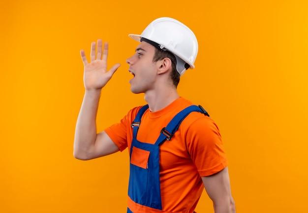 Uomo giovane costruttore indossa uniforme da costruzione e chiamate casco di sicurezza Foto Gratuite