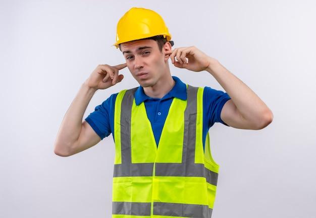 Uomo giovane costruttore indossa uniforme da costruzione e casco di sicurezza che copre le orecchie con le dita Foto Gratuite