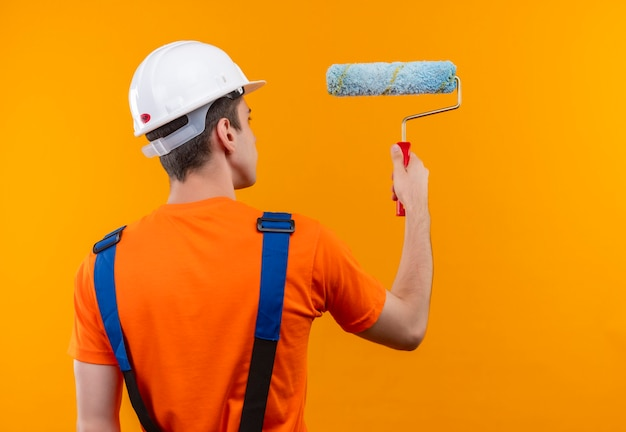 Young builder man wearing construction uniform and safety helmet paints the wall with a roller brush Free Photo