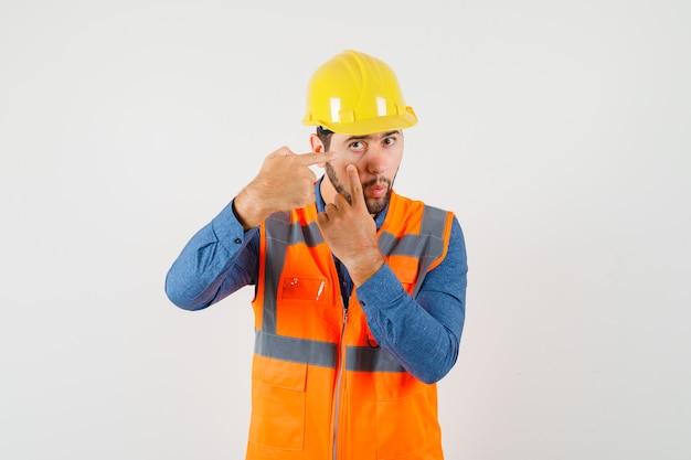Giovane costruttore in camicia, giubbotto, casco che punta alla palpebra tirato da un dito, vista frontale. Foto Gratuite