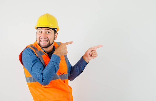 Young builder in shirt, vest, helmet pointing to the side and looking curious , front view. Free Photo