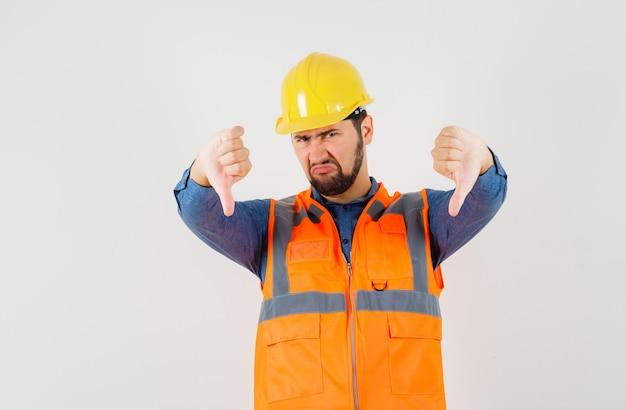 Giovane costruttore che mostra i doppi pollici in giù in camicia, gilet, casco e sembra deluso, vista frontale. Foto Gratuite