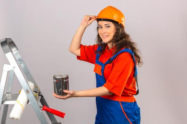 Giovane donna del costruttore in uniforme della costruzione e casco di sicurezza su una scala del metallo con la latta della pittura che sorride e che tocca il suo casco sopra la parete bianca isolata Foto Gratuite