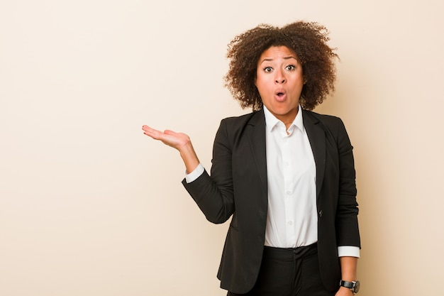 Young business african american woman impressed holding copy space on palm. Premium Photo