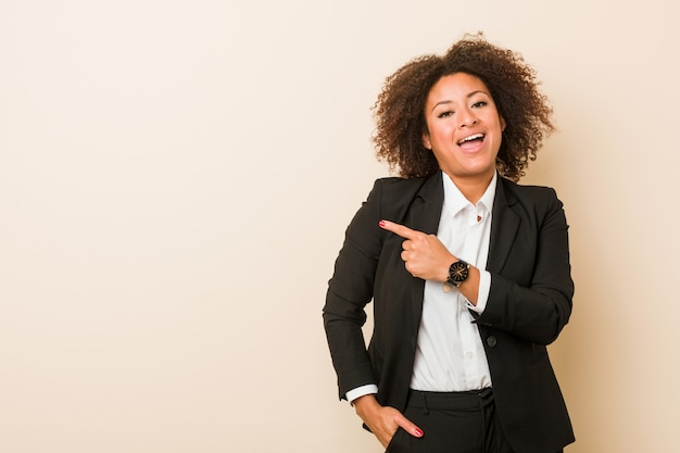 Young business african american woman smiling and pointing aside, showing something at blank space. Premium Photo