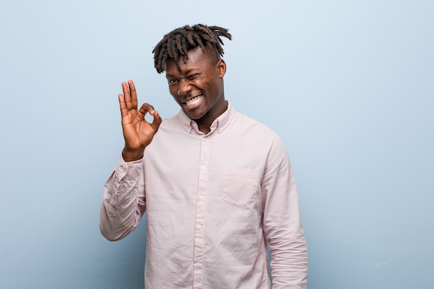 Young business african black man winks an eye and holds an okay gesture with hand. Premium Photo