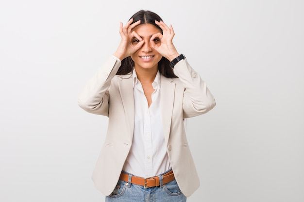 Young business arab woman isolated against a white background showing okay sign over eyes Premium Photo
