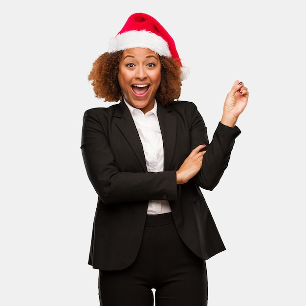 Young business black woman wearing a chirstmas santa hat pointing to the side with finger Premium Photo