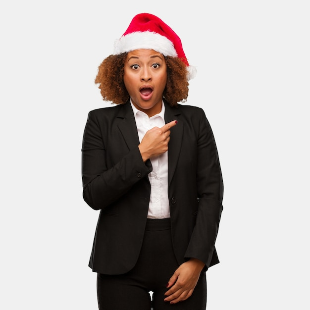 Young business black woman wearing a chirstmas santa hat pointing to the side Premium Photo
