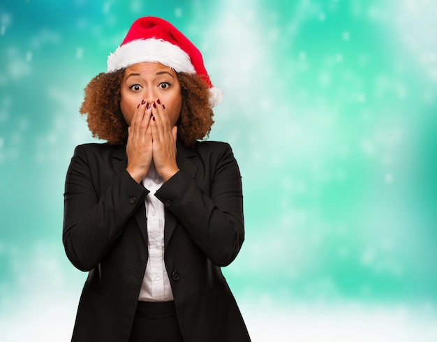 Young business black woman wearing a chirstmas santa hat very scared and afraid hidden Premium Photo