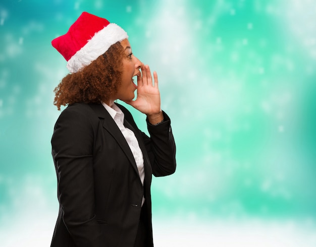 Young business black woman wearing a chirstmas santa hat whispering gossip undertone Premium Photo