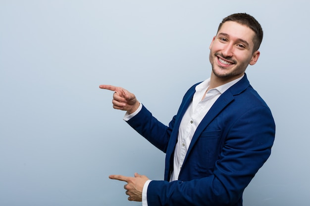 Young business caucasian man excited pointing with forefingers away. Premium Photo