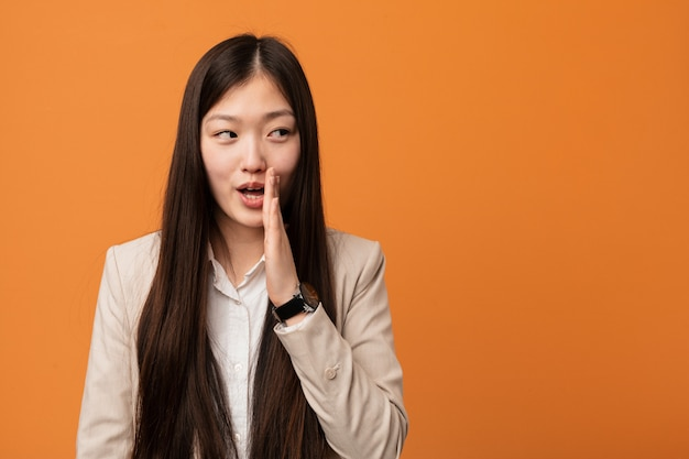 Young business chinese woman is saying a secret hot braking news and looking aside Premium Photo