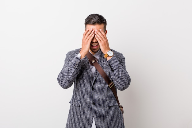 Young business filipino man against a white wall covers eyes with hands, smiles broadly waiting for a surprise. Premium Photo