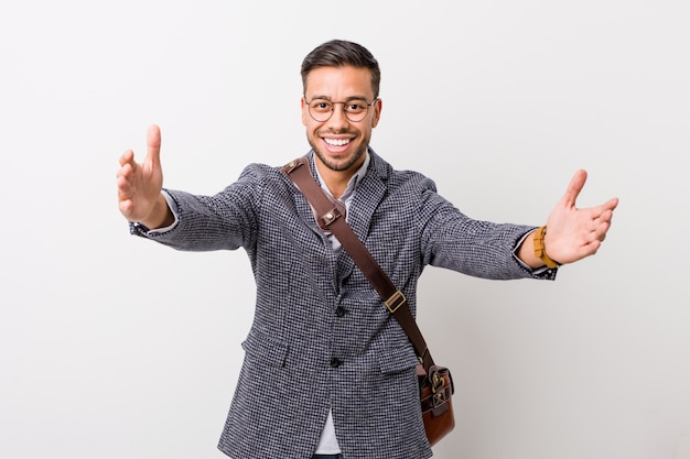 Young business filipino man against a white wall feels confident giving a hug to the camera. Premium Photo