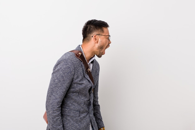 Young business filipino man against a white wall shouting towards a copy space Premium Photo