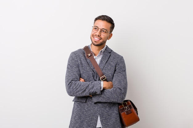 Young business filipino man against a white wall smiling confident with crossed arms. Premium Photo