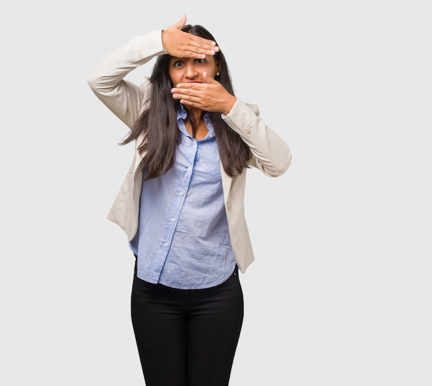 Young business indian woman looking through a gap, hiding and squinting Premium Photo