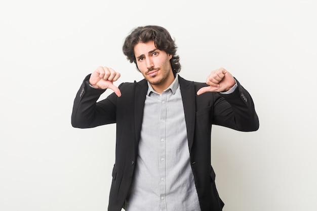 Young business man against a white wall showing thumb down and expressing dislike. Premium Photo