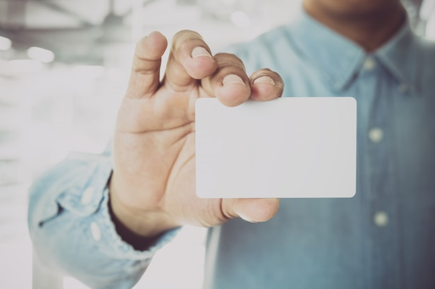 Young business man holding white business card on modern office blur background. Premium Photo