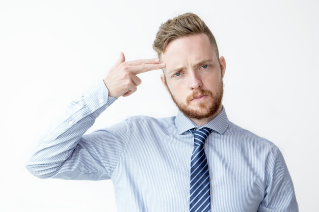 Young business man shooting himself with fingers Free Photo