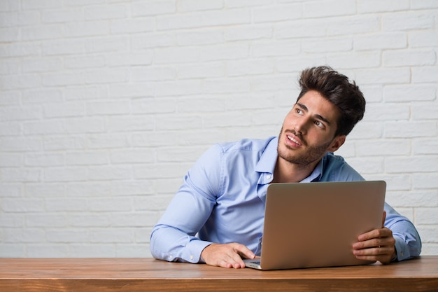Young business man sitting and working on a laptop looking up, thinking of something fun and having an idea, concept of imagination, happy and excited Premium Photo