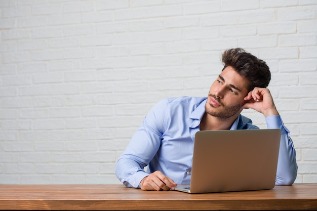 Young business man sitting and working on a laptop looking up Premium Photo