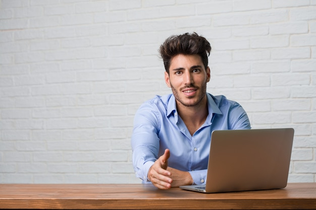 Young Business Man Sitting And Working On A Laptop Reaching Out To
