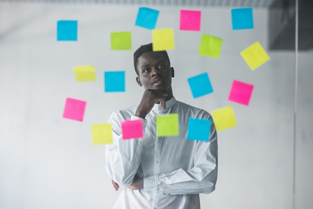 Young business man standing in front of stickers glass wall and looking on futures plans at his office place Free Photo