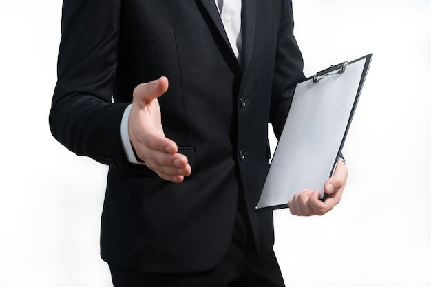 사인 보드를 잡고 악수를주는 동안 양복을 입고 젊은 비즈니스 사람. 프리미엄 사진