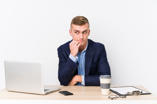 Young business man with a laptop confused, feels doubtful and unsure. Premium Photo