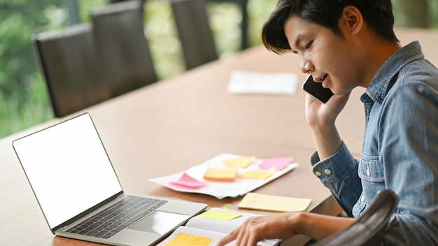 Young business men are calling to work and use laptop. Premium Photo