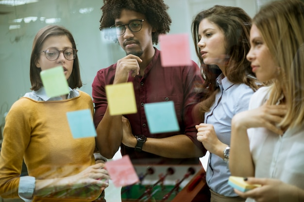 Young business people discussing in front of glass wall using post it notes and stickers Premium Photo