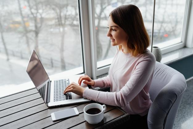 젊은 비즈니스는 Netbook 키보드에 입력하고 음악을 듣고. 무료 사진