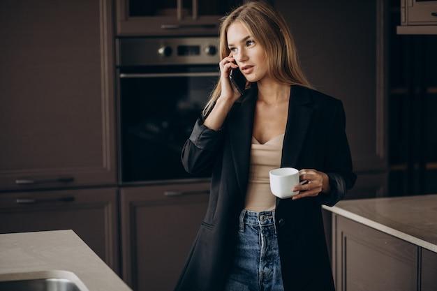 コーヒーを飲み、キッチンで電話で話している若いビジネス女性 無料写真